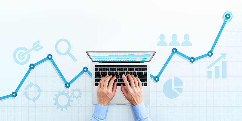 Hands typing on a lap top with an increasing line graph in the background.